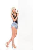 Blondes Mädchen, das mit großer weißer Fahne aufwirft Stockbilder