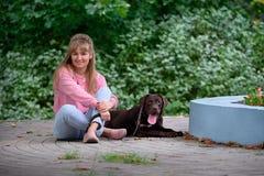 Blondes Mädchen, das mit Hund Labrador lächelt Labrador, das als Nächstes liegt Stockbild