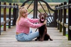 Blondes Mädchen, das mit Hund Labrador lächelt Labrador, das als Nächstes sitzt Lizenzfreies Stockfoto