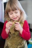 Blondes Mädchen, das mit kleinen Puppen spielt Lizenzfreies Stockbild