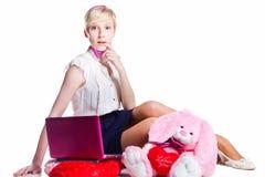 Blondes Mädchen, das mit rosafarbenem Laptop arbeitet Lizenzfreies Stockfoto