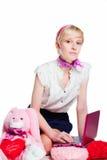 Blondes Mädchen, das mit rosafarbenem Laptop arbeitet Lizenzfreies Stockbild