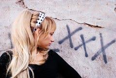 Blondes Mädchen, das nahe dem Schreiben auf der Wand aufwirft Lizenzfreie Stockfotos