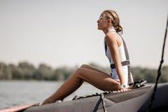 Blondes Mädchen, das nahe dem See auf dem Pier sitzt lizenzfreie stockfotografie