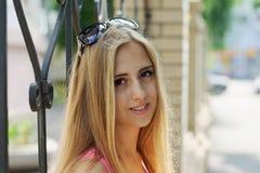 Blondes Mädchen, das nahe dem Zaun steht Lizenzfreie Stockbilder