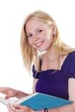 Blondes Mädchen, das oben vom Studienbuchlächeln schaut Lizenzfreie Stockfotos
