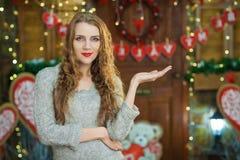 Blondes Mädchen, das Produkt auf leerem Kopienraum der Palme zeigt Stockfotos