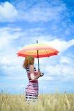 Blondes Mädchen, das Regenschirm und Stellung in Goldenem hält Stockfotos