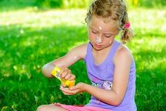 Blondes Mädchen, das Sonnencreme im Garten verwendet lizenzfreies stockbild