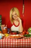 Blondes Mädchen, das am Tisch sitzt Lizenzfreie Stockfotos