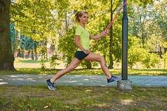 Blondes Mädchen, das Trainings mit Eignung trx Streifen tut Lizenzfreie Stockfotografie