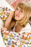 Blondes Mädchen, das unter einer Decke mit Basisrecheneinheiten liegt Lizenzfreie Stockfotos