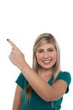 Blondes Mädchen, das weg auf weißen Hintergrund zeigt Stockbild