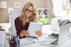 Blondes Mädchen, das zu Hause arbeitet Lizenzfreie Stockfotos