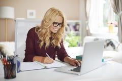 Blondes Mädchen, das zu Hause arbeitet lizenzfreie stockfotografie