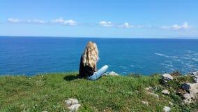 Blondes Mädchen, das zurück auf dem Felsen sitzt Stockfoto