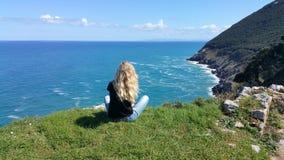 Blondes Mädchen, das zurück auf dem Felsen sitzt Stockfotos