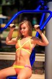 blondes Mädchen in den Bikinizügen auf Gewichtsstapelsimulator im Park Lizenzfreies Stockfoto