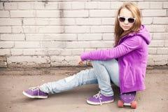 Blondes Mädchen in den Jeans und in der Sonnenbrille sitzt auf Skateboard Lizenzfreie Stockfotografie