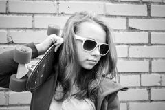 Blondes Mädchen in den Jeans- und Sonnenbrillegriffen fahren Skateboard Lizenzfreie Stockfotos