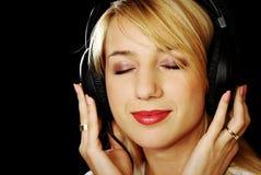 Blondes Mädchen in den Kopfhörern mit den Augen geschlossen Stockbild