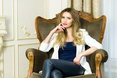Blondes Mädchen in den ledernen Hosen, die in einer Couch sitzen lizenzfreies stockbild