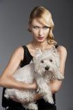 Blondes Mädchen der alten Art und Weise, hat sie einen Hund in ihren Armen Stockbilder