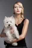 Blondes Mädchen der alten Art und Weise, hat sie einen Hund in ihren Armen Lizenzfreie Stockfotos