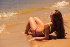 Blondes Mädchen in der Bikininahaufnahmerückseite liegt an zurück durch Meer Lizenzfreies Stockbild