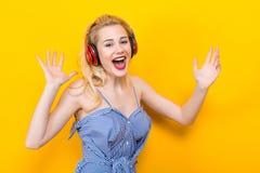 Blondes Mädchen in der blauen gestreiften Bluse mit Kopfhörern Lizenzfreies Stockfoto