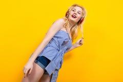 Blondes Mädchen in der blauen gestreiften Bluse mit Kopfhörern Lizenzfreie Stockfotografie