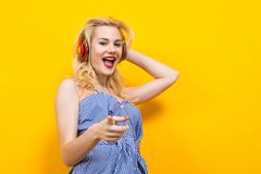 Blondes Mädchen in der blauen gestreiften Bluse mit Kopfhörern Stockbilder
