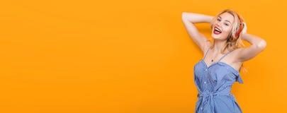 Blondes Mädchen in der blauen gestreiften Bluse mit Kopfhörern Stockfoto