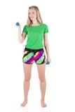 Blondes Mädchen in der bunten Sportkleidung, die mit den Beinen auf der Schulterbreite hält blaue Dummköpfe in den Händen steht Lizenzfreie Stockfotos