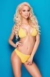 Blondes Mädchen in der gelben Bikiniaufstellung Lizenzfreie Stockfotos