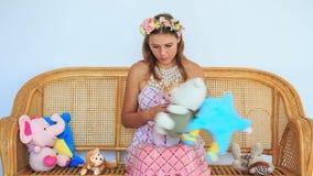 Blondes Mädchen in der Girlande betrachtet Kinderspielwaren im Lehnsessel stock video footage