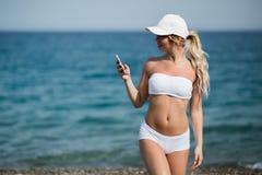 Blondes Mädchen der glücklichen hübschen Eignung zeigt Mobiltelefon und das Lächeln Lizenzfreies Stockfoto
