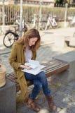 Blondes Mädchen an der Holzbank, die ihre Anmerkungen scannt Lizenzfreies Stockfoto