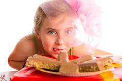 Blondes Mädchen der hungrigen Geste Kinderin den Parteischokoladen Lizenzfreie Stockfotografie
