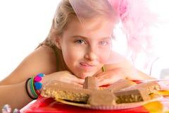 Blondes Mädchen der hungrigen Geste Kinderin den Parteischokoladen Stockbilder