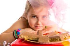 Blondes Mädchen der hungrigen Geste Kinderin den Parteischokoladen Lizenzfreie Stockbilder