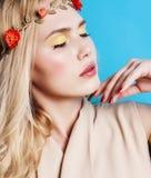 Blondes Mädchen der Junge recht mit dem gelockten blonden Haar und glückliches Lächeln der kleinen Blumen auf Hintergrund des bla Lizenzfreies Stockfoto