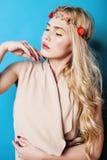 Blondes Mädchen der Junge recht mit dem gelockten blonden Haar und wenig senkt das glückliche Lächeln auf Hintergrund des blauen  Lizenzfreie Stockfotografie