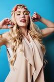 Blondes Mädchen der Junge recht mit dem gelockten blonden Haar und wenig senkt das glückliche Lächeln auf Hintergrund des blauen  Lizenzfreie Stockbilder