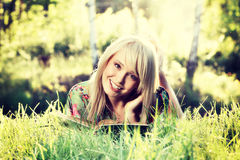Blondes Mädchen der jungen Frau, das in einem Parklesebuch, Sitzen allein auf Gras sich entspannt Lizenzfreie Stockfotos