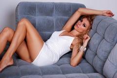 Blondes Mädchen der Mode, das auf einem Sofa liegt Stockbilder