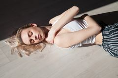 Blondes Mädchen der Mode liegt auf den geschlossenen Bodenaugen Stockbilder