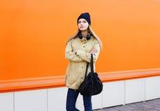 Blondes Mädchen der Mode recht, das über Orange aufwirft Stockfotos
