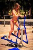 blondes Mädchen der Nahaufnahme im Bikini bildet auf Stepper auf Sportplatz aus Lizenzfreie Stockfotos