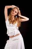 Blondes Mädchen der Neigung im weißen Kleid mit dem angehobenen Arm lizenzfreie stockbilder